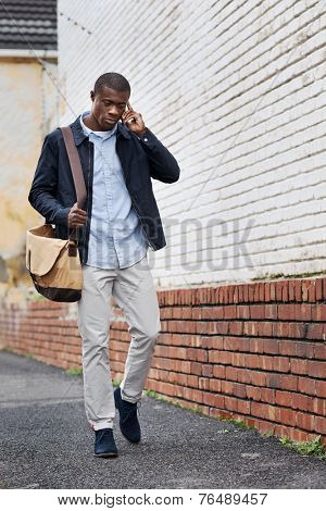 african black man walking and talking on cell phone in city on way to work