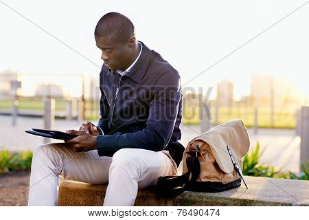 African black business man hipster using tablet computer in park on break from work
