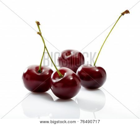 Four cherries close-up on white background