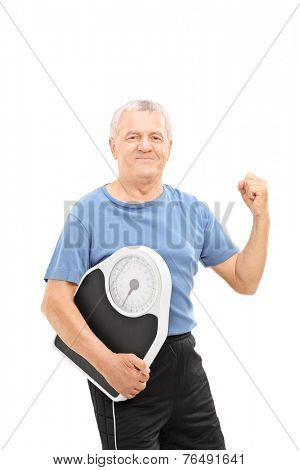 Happy senior with gripped fist holding a weight scale isolated on white background