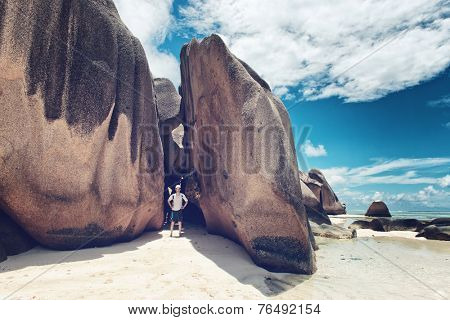 Tourist Posing at Large Granite Rocks at Famous Anse Source d'Argent in La Digue Island, Seychelles.