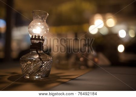 Antique oil lamp with dim light on table in cafe
