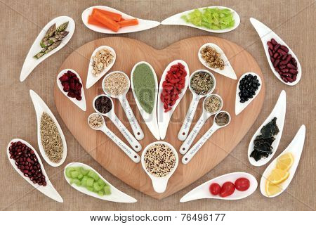 Large healthy heart super food selection in porcelain bowls and measuring spoons over brown paper background.