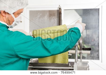 Cropped image of male chef unwrapping pasta sheet from rolling pin into machine at commercial kitchen