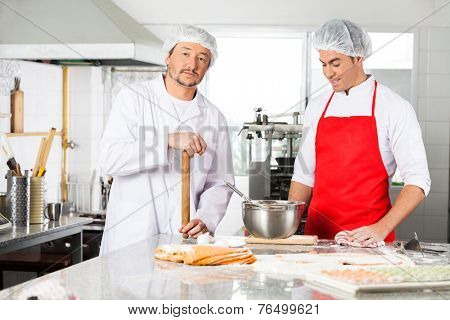 Portrait of confident male chef standing with colleague preparing ravioli pasta at commercial kitchen counter
