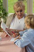 stock photo of grandma  - Vertical view of grandma teaching his grandson - JPG