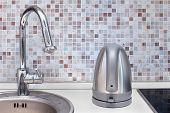 stock photo of kettles  - Modern electric silver kettle on kitchen counter - JPG