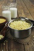 pic of millet  - Millet porridge in a metal pan on the wooden table - JPG
