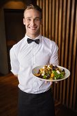 foto of waiter  - Smiling waiter showing plate of salad to camera in a bar - JPG