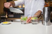 stock photo of bartender  - Happy bartender making a cocktail in a bar - JPG