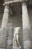 stock photo of beheaded  - Beautiful greek statue of marble man without head between dorian columns - JPG