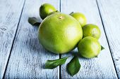 image of sweetie  - Ripe sweetie and limes on wooden background - JPG