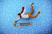 foto of toboggan  - Happy young man on sled having fun against the blue background with snowflakes - JPG