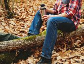 stock photo of thermos  - Unrecognizable hiker man holding a cup of tea or coffee and thermos and sitting on tree trunk in autumn forest - JPG