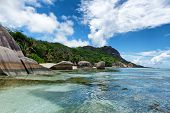 Beautiful Natural View of Anse Source d'Argent with Rocks and Mountains on the Beach Side at La Digue. A Tourist Destination in Seychelles. poster