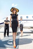 image of bodyguard  - Full length of beautiful woman in elegant dress with bodyguard and airhostess standing against private plane - JPG