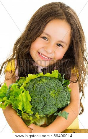 Adorable healthy little girl holding salad bowl with broccoli and lettuce
