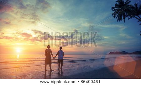 Silhouette of young couple on their honeymoon standing on Sea beach at amazing sunset.