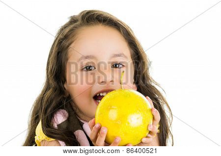 Adorable healthy little girl holding a passionfruit in front of her face