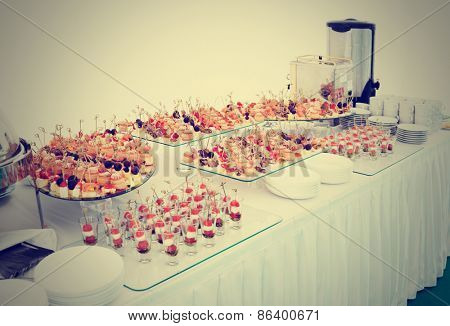 Various meat, fish and cheese banquet snacks on banquet table, toned image