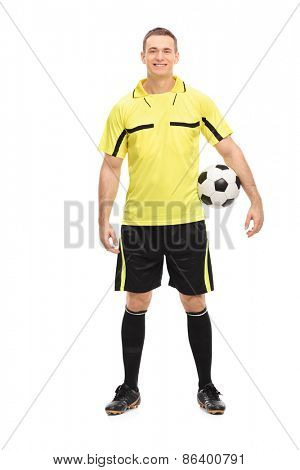 Full length portrait of a male football referee in a yellow jersey holding a ball isolated on white background