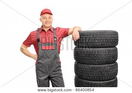 Male mechanic in a red shirt and gray jumpsuit leaning on a stack of tires isolated on white background