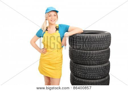 Beautiful female mechanic in a yellow uniform and a blue cap standing next to a stack of tires isolated on white background