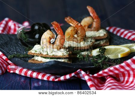 Appetizer canape with shrimp and olives on plate on table close up