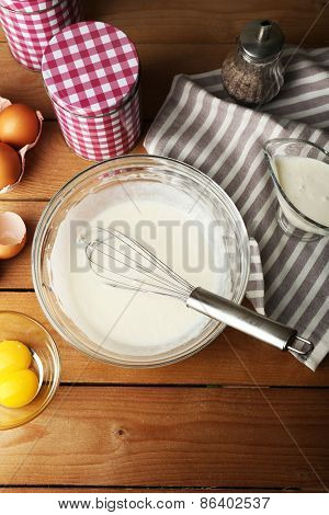 Preparation cream with eggs in glass bowl on wooden table, top view