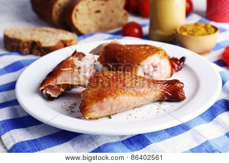 Smoked chicken with vegetables on plate on table close up