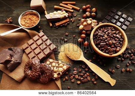 Still life with set of chocolate, nuts and spices on wooden table, closeup