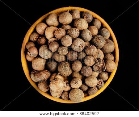 Allspice in wooden bowl, isolated on black