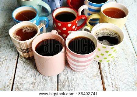 Many cups of coffee on wooden table, closeup
