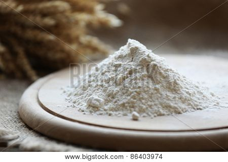 Pile of flour on cutting board with burlap cloth, closeup