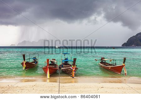Boats in the tropical sea under gloomy dramatic sky. Thailand