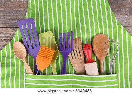 Set of kitchen utensils in pocket of apron, closeup