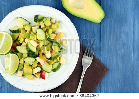 Salad with apple and avocado in bowl on table close up