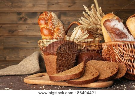 Different bread with ears in basket on wooden background
