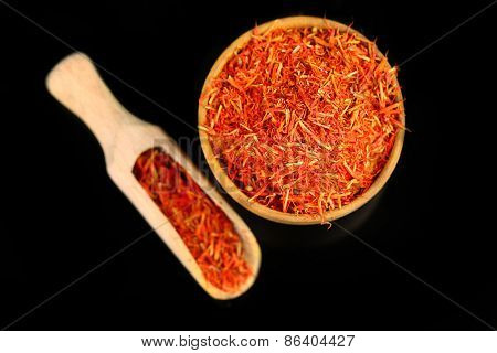 Saffron in wooden bowl, isolated on black