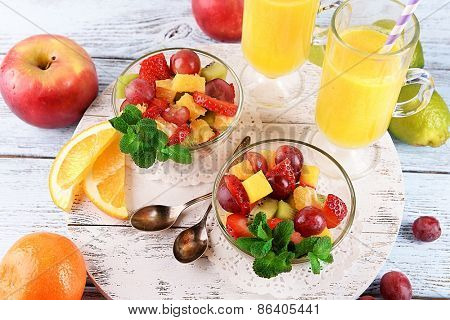 Fruit salad with mint and orange juice in glassware on color wooden background