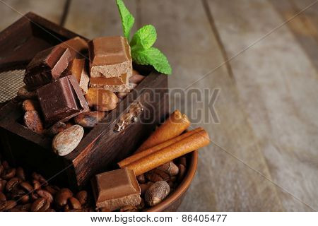 Still life with set of chocolate, coffee beans and spice on wooden table, closeup