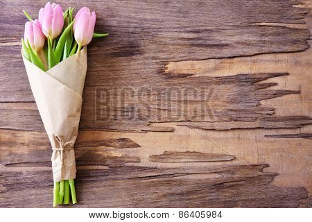 Beautiful pink tulips in paper on wooden background