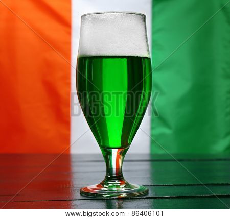 Glass of green beer on Ireland flag background