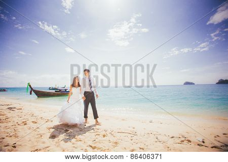 Young Brunette Bride And Groom Walk Hand In Hand