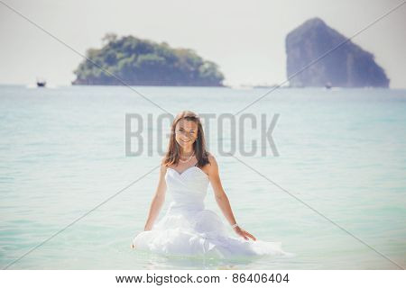 Bride In White Dress Smile Standing In Azure Water