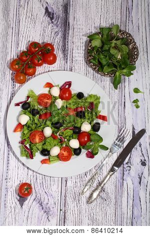Salad With Tomatoes, Mozzarella, Olives, Cabbage And Ruccola And Olive Oil