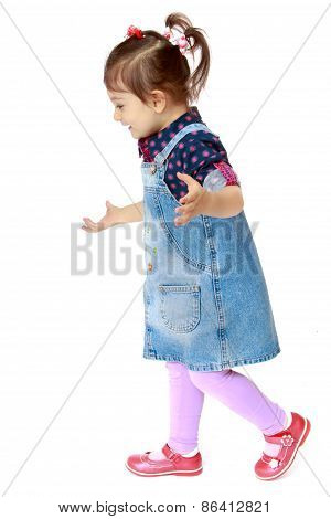 Little girl in a denim dress on white background