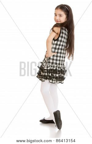 Dark haired girl posing in a plaid dress and white stockings