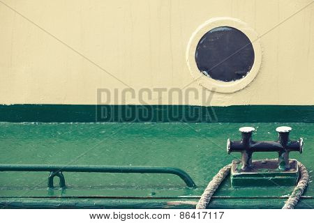 Old Round Porthole And Black Mooring Bollard