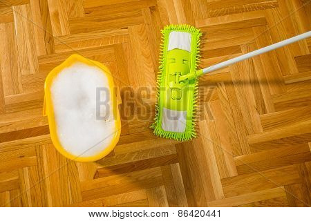 Cleaning the floor with a mop. Yellow bucket is filled with water and foam.